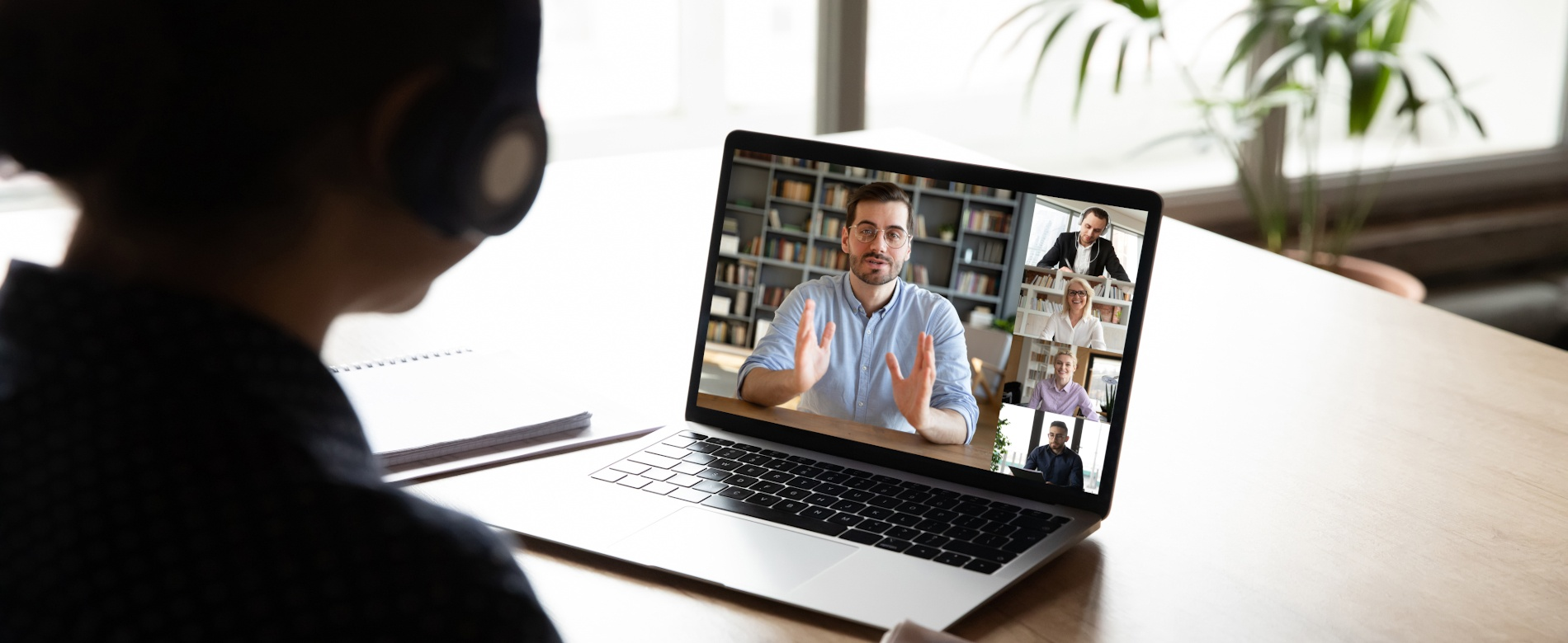 E-learning via virtual application, videocall video conferencing activity, colleagues working together concept. Pc screen view over woman shoulder, listen tutor gain new knowledge noting information